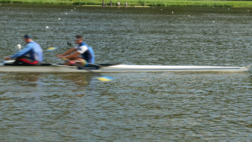 A 4 men rowing boat cuts through the water, enters and leaves the shot. Medium shot.