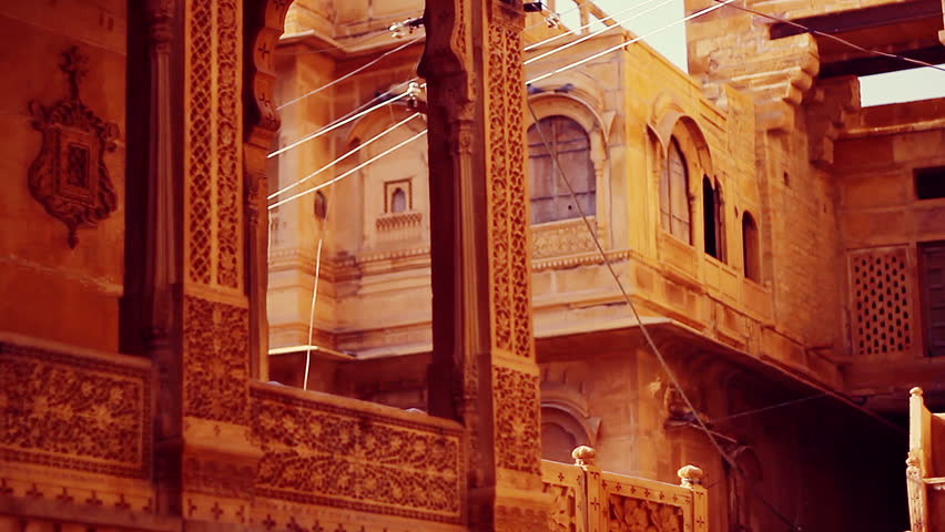 Tracking shot of Jaisalmer Fort's sandstone havelis with its elaborately sculpted columns, windows and balconies, under a golden sunset light.