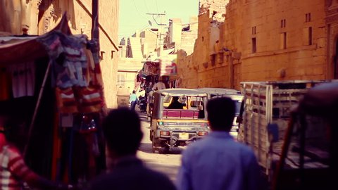 Rickshaw (tuk-tuk) riding through a narrow cobbled street of the ancient fortress of Jaisalmer, India. A market is partially visible and several people go by on the foreground. Shallow DOF.