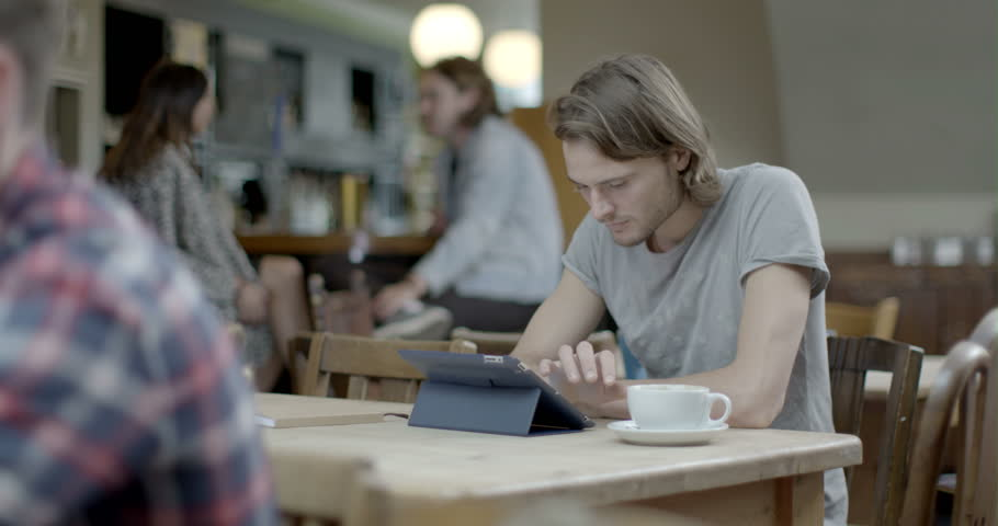 Man using digital tablet and drinking coffee while sitting in pub | Shutterstock HD Video #8044387