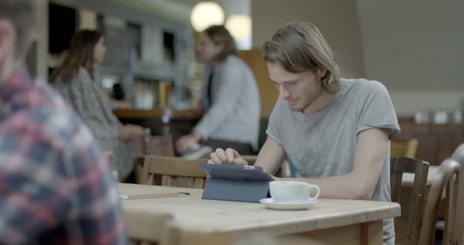 Man using digital tablet while sitting in pub   Shutterstock HD Video #8044396