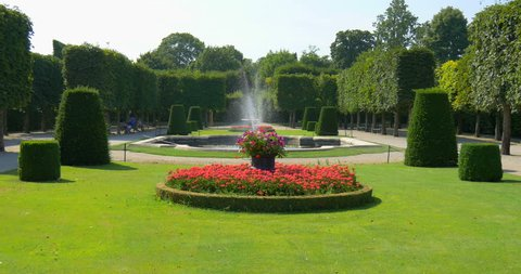Beautiful garden landscape with flowers, green grass, fountain in the Schonbrunn royal imperial palace park in Vienna city (Wien), Austria, Europe. Summer travel to famous attraction place background