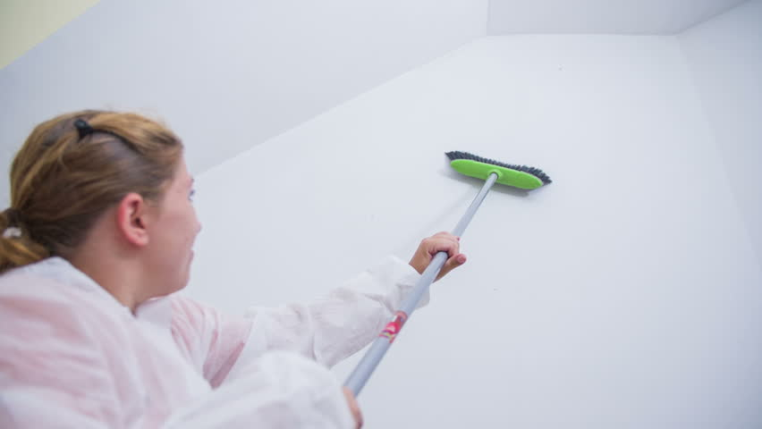 Woman cleaning spiderwebs from walls with broom. Slow motion shot of female in protective clothes working in new abandoned apartment cleaning spiderwebs before painting.   Shutterstock HD Video #8070334