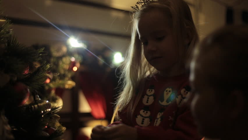 Little blond girl with long hair dressed in a red sweater with snowmens decorates Christmas tree with her mother in the dark | Shutterstock HD Video #8076367