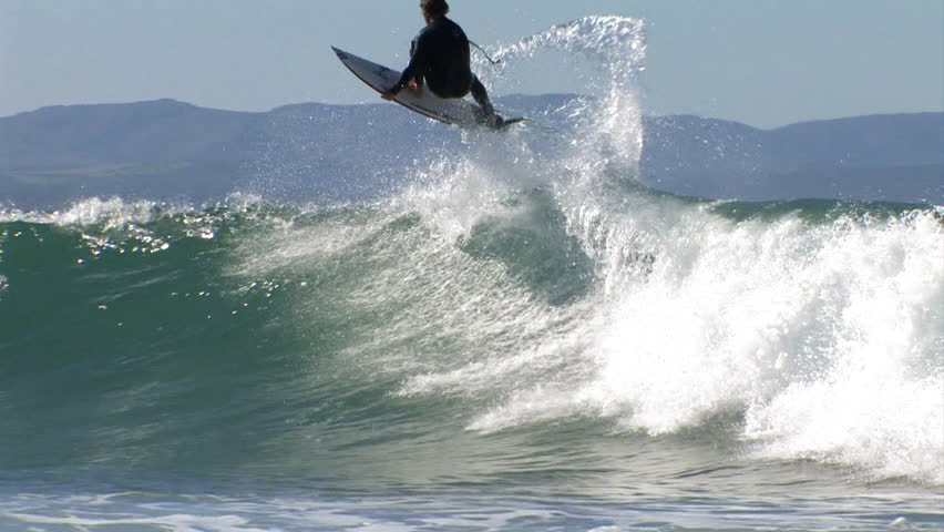 A surfer performs a jump and turn on a nice wave | Shutterstock HD Video #8099827