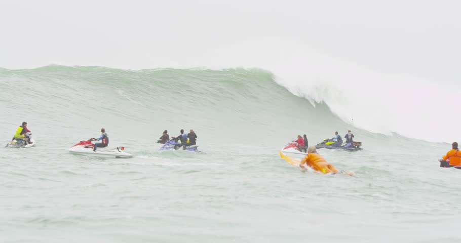 PERU - JULY 03, 2014: Big Wave World Tour- Big wave crashing with people on jet skis in water, surfer paddling. Boat angle. | Shutterstock HD Video #8103337