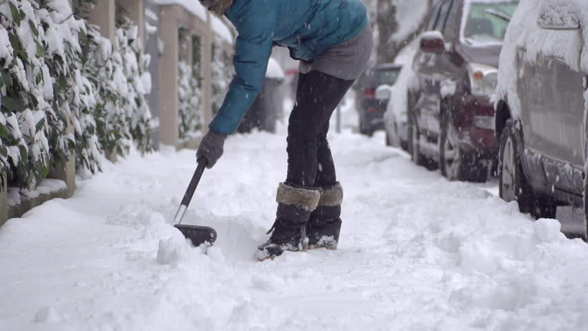 Slow Motion Of A Female Shoveling Snow Off The Pavement After Blizzard