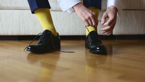 The man in a yellow socks wears shoes to tie shoelaces.