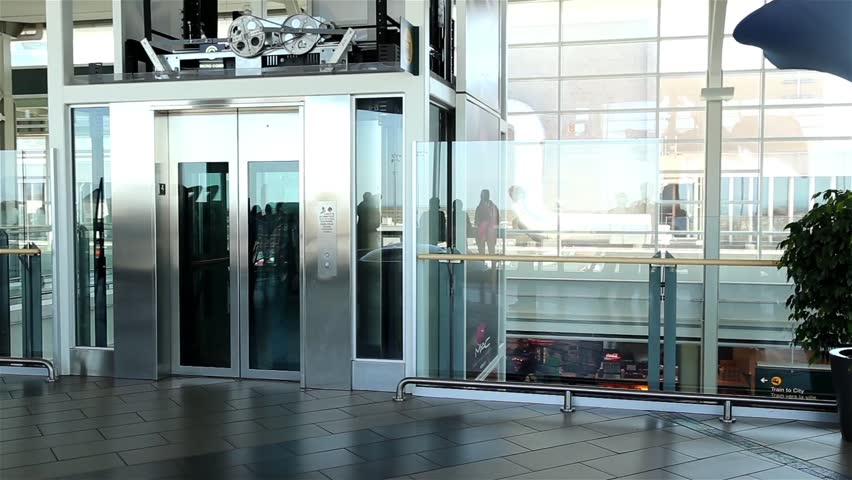 Burnaby, BC, Canada - September 13, 2014 : Motion of people taking elevlator inside YVR airport in Vancouver BC Canada. #8126887