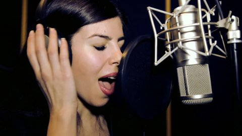 Young beautiful girl sings.Young singer singing into a microphone.Portrait close up of the singer.Recording studio.Recording in the studio singers.