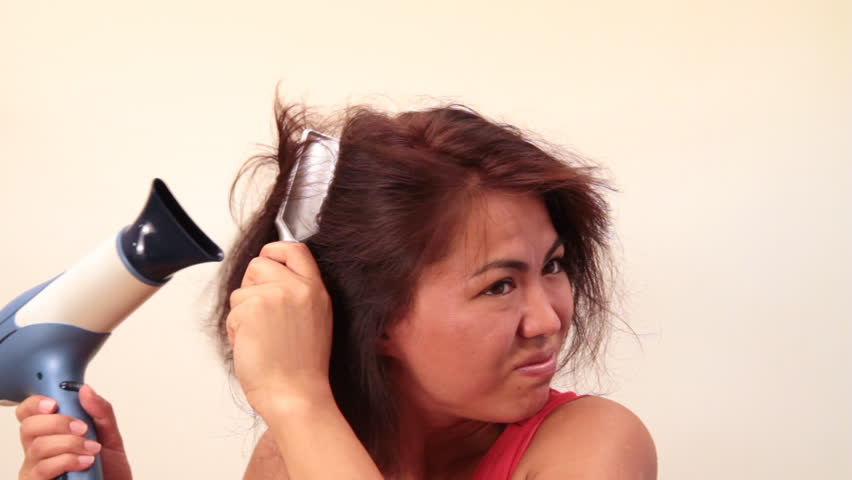 Woman holding a hair dryer has bad hair day (combs sticks in her hair)