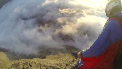 A base jumper in a wingsuit jumps down from a cliff, passes through clouds while gliding over a landscape, POV