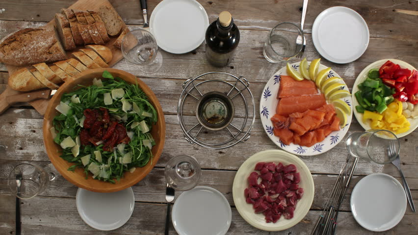Eating with friends time-lapse, top view of fondue party served on vintage wooden table