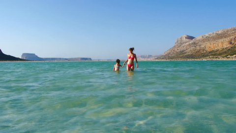 Mother and daughter walking in the sea, surrounded by beautiful scenery