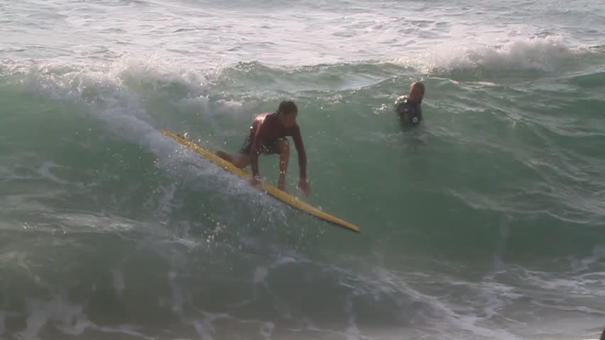 A surfer paddles the longboard, tries to ride the wave but loses and falls as the wave starts to rise | Shutterstock HD Video #8302987