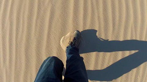 High angle shot of legs and feet of a man walking in a sandy desert. Handheld shot showing hiker and shoes kicking up sand as he shuffles and walks.