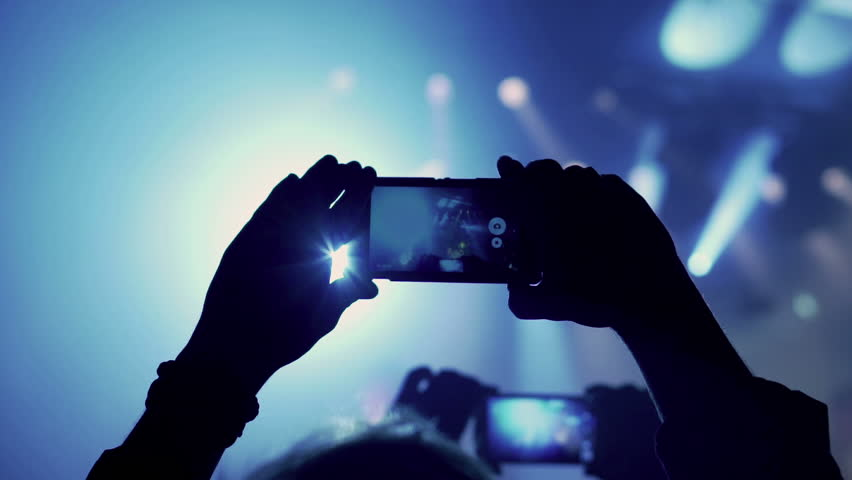 Person records rock concert on cellphone in the club, steadycam shot