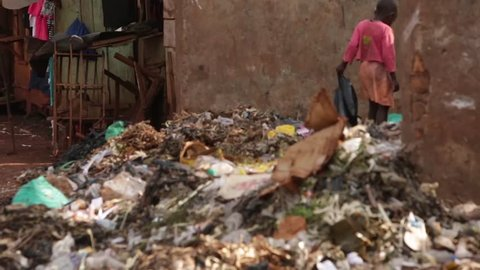 MOSHI, TANZANIA - MARCH 2013: Young African child looking through a rubbish pit in a slum in Africa