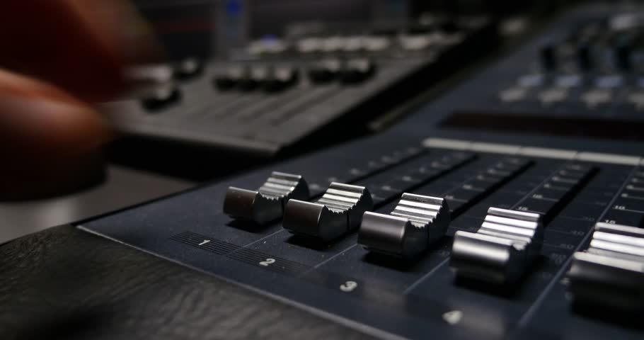 4K footage of a recording studio´s audio console and a hand pulling up the knobs/The audio console