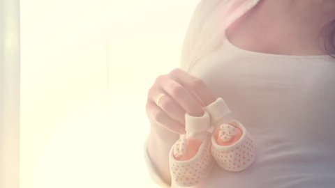 Beautiful Pregnant woman Playing with kid bootees. Little baby shoes stepping on her belly. Pregnancy. Parenthood concept, sunlight in room. Slow motion high speed camera shot 240 fps, HD 1080