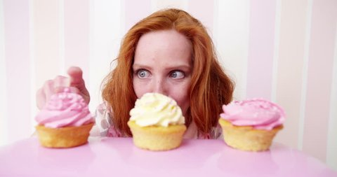 Young redhead woman really wants to eat pink cupcakes