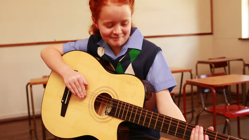 Front view of cute smiling Caucasian  pupil playing guitar in classroom at the elementary school #8414797