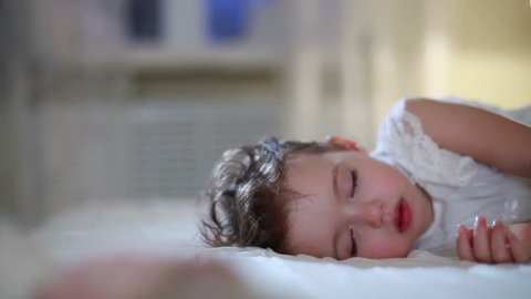 Adorable little girl in a white dress sleeping with her toys. Dolly shot. Close-up.