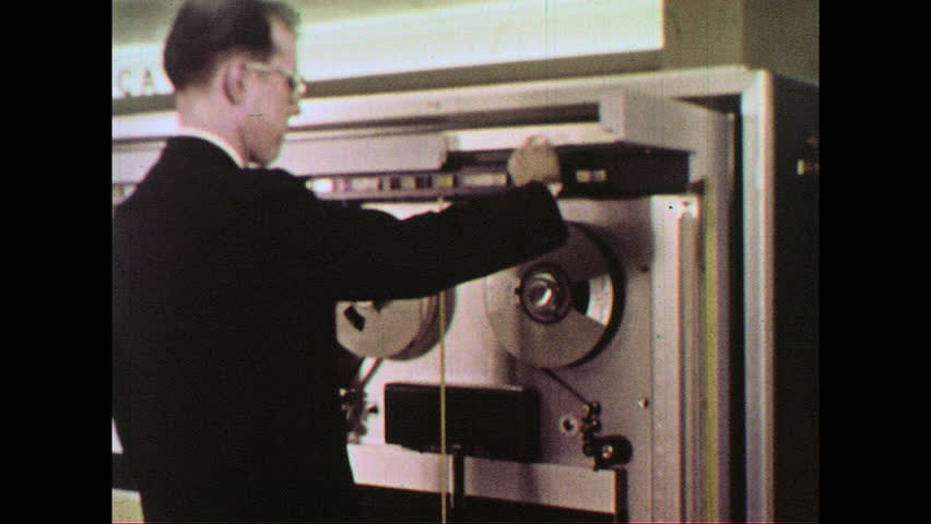 UNITED STATES 1960s :A man feeds the magnetic tape into a computer which is processed by a console operator.