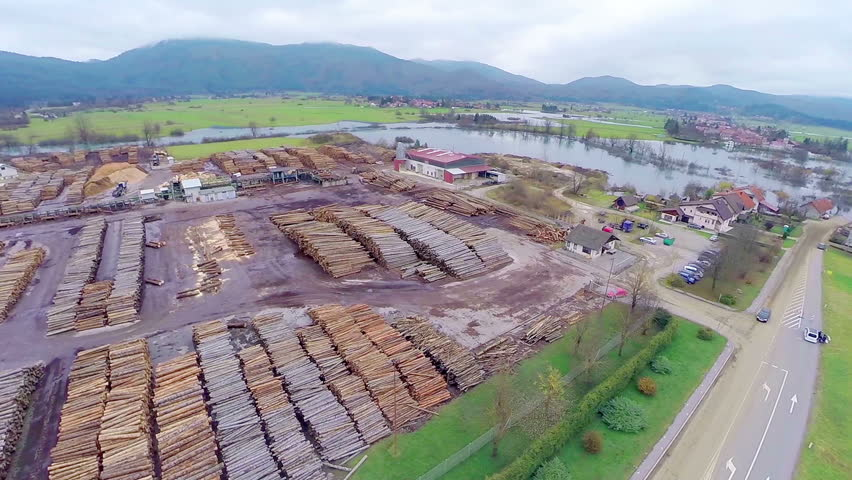 AERIAL: Wood industry. Flying over wood sawing industrial place, with a lot of stock of firewood. | Shutterstock HD Video #8453377