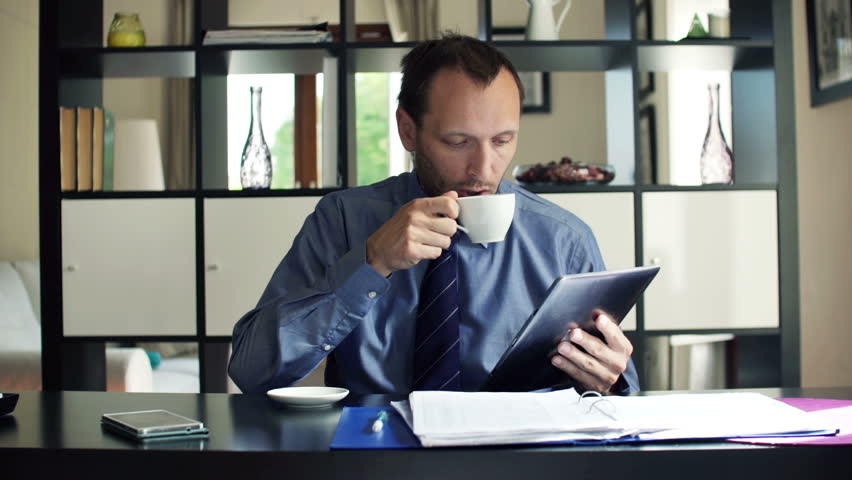 Businessman reading article on tablet computer and drinking coffee at home  | Shutterstock HD Video #8457697