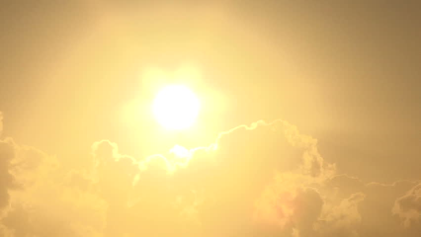 Close up of bright shining sun rising above clouds.