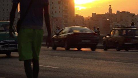 La Havana, Cuba - December 26, 2014: La Habana vieja, view of old vintage cars on Malecon at sunset, with people sitting near the sea