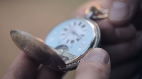 A man looks at the time of old pocket watches and closes them. Close up