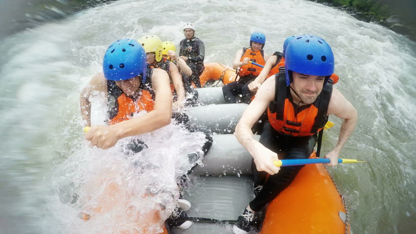 White water rafting team of seven people, large waves hitting the raft, includes audio