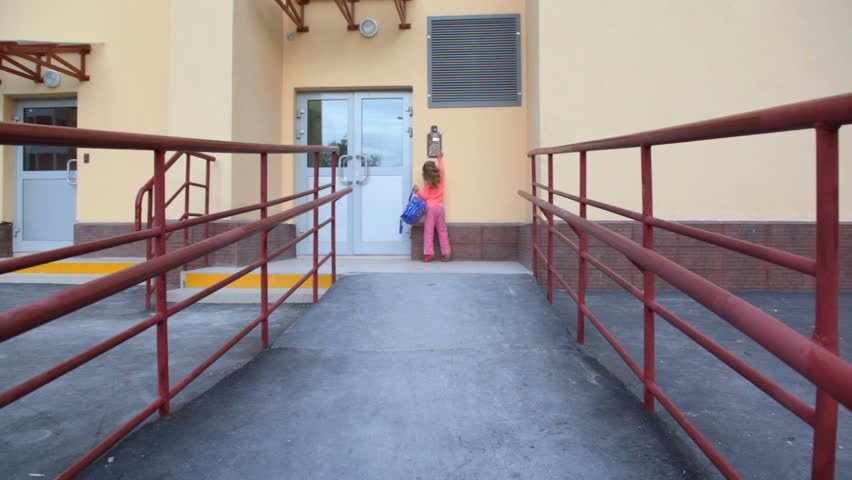 little girl with rucksack using door intercommunication system