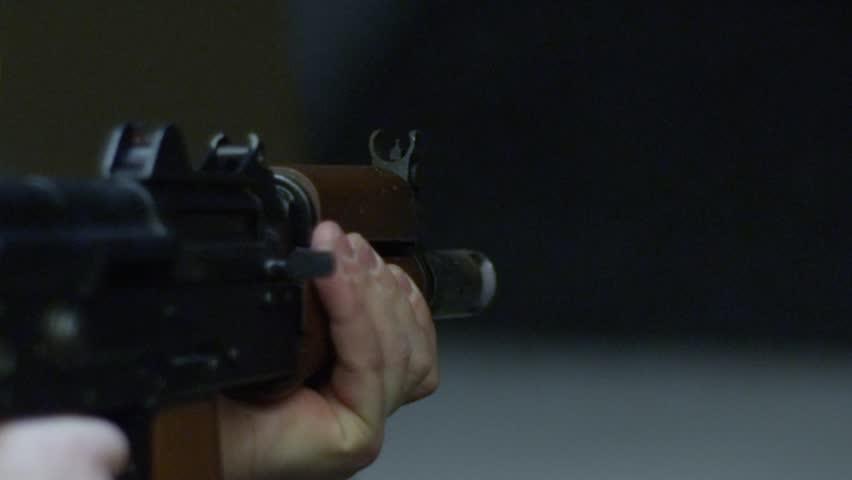 Firing a machine gun in slow motion at gun range