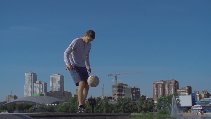 Low angle of soccer freestyler juggling soccer ball on his back standing on the bridge