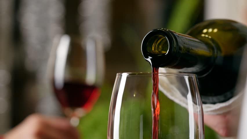 Sommelier filling glass with wine in restaurant. 4K, UHD