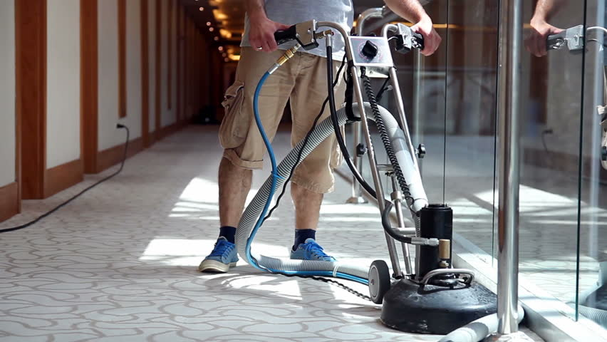 Cleaner male worker with carpet cleaning machine cleaning hotel corridor carpet. Hotel carpet washing machine. Hotel cleaning service.