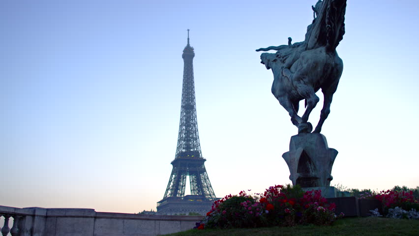 A crane shot of the France Reborn statue and the Eiffel Tower at Pont De Bir-Hakeim/Pont De Passy during the early morning hours in Paris, France.