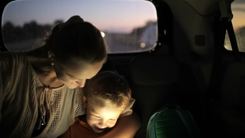Tilt shot of mother and son using tablet computer while traveling on backseat of a car at night