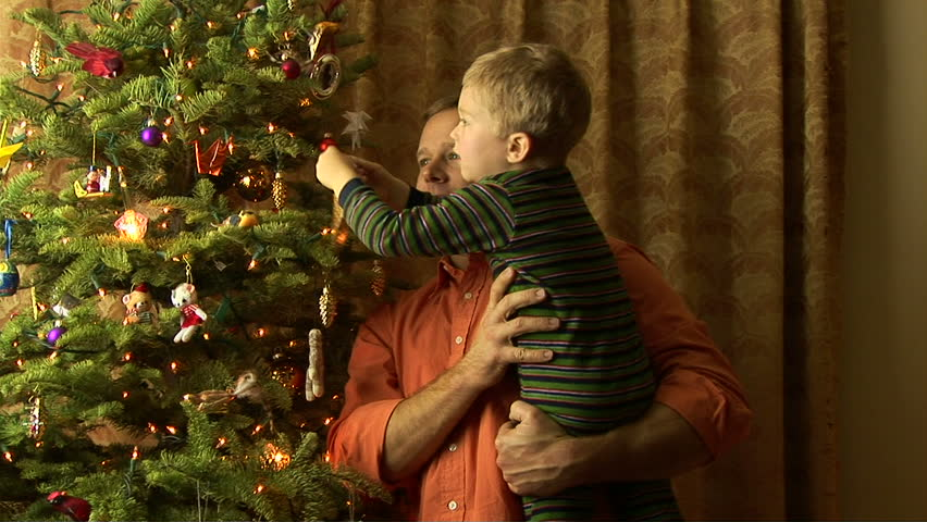 Father helping son decorate Christmas tree