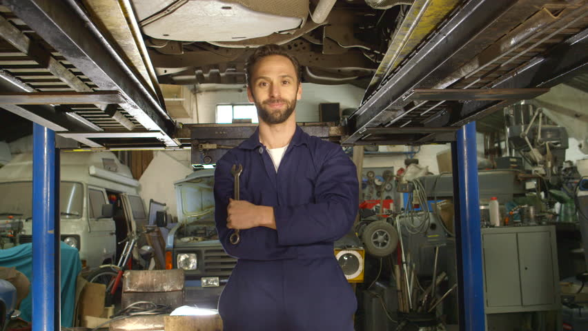 Portrait of a young mechanic working under a car | Shutterstock HD Video #8699578
