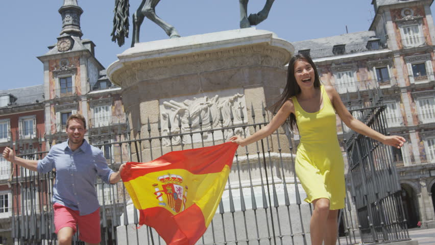 Spanish flag. People cheering celebrating showing Spain flag in Madrid on Plaza Mayor. Happy excited young woman and man running with flags towards camera on the famous square. RED EPIC SLOW MOTION.