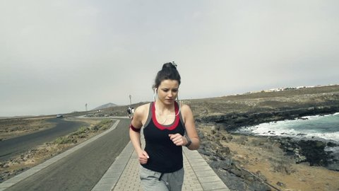 Young woman with smartwatch jogging by sea, slow motion shot at 240fps