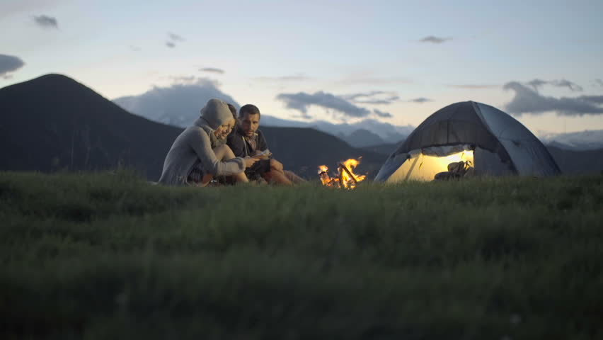 Group Of Three Friends Warming With Camp-fire In Nature ...
