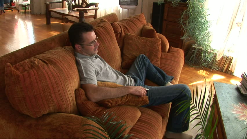 Young man on couch using remote to watch TV