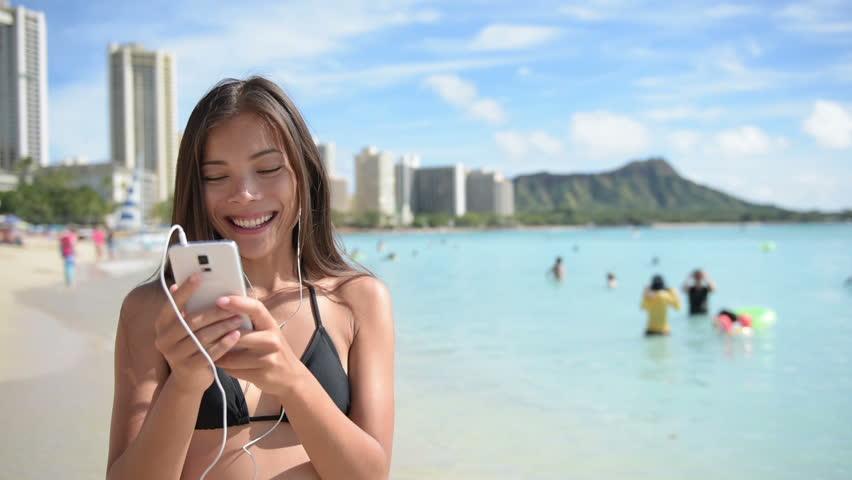 Woman using mobile cell smart phone laughing on beach wearing earphones for music or talking Girl in bikini using smartphone happy. Beautiful Asian Caucasian female model on Waikiki, Oahu, Hawaii, USA