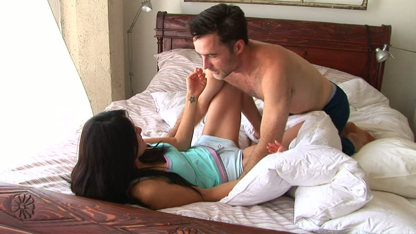 Young couple in bed kissing