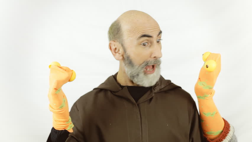 A friar (Franciscan religious man) playing with two handmade sock puppets. White background.